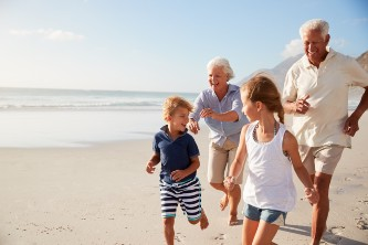 grandparents and their grandchildren running on the beach on a sunny day