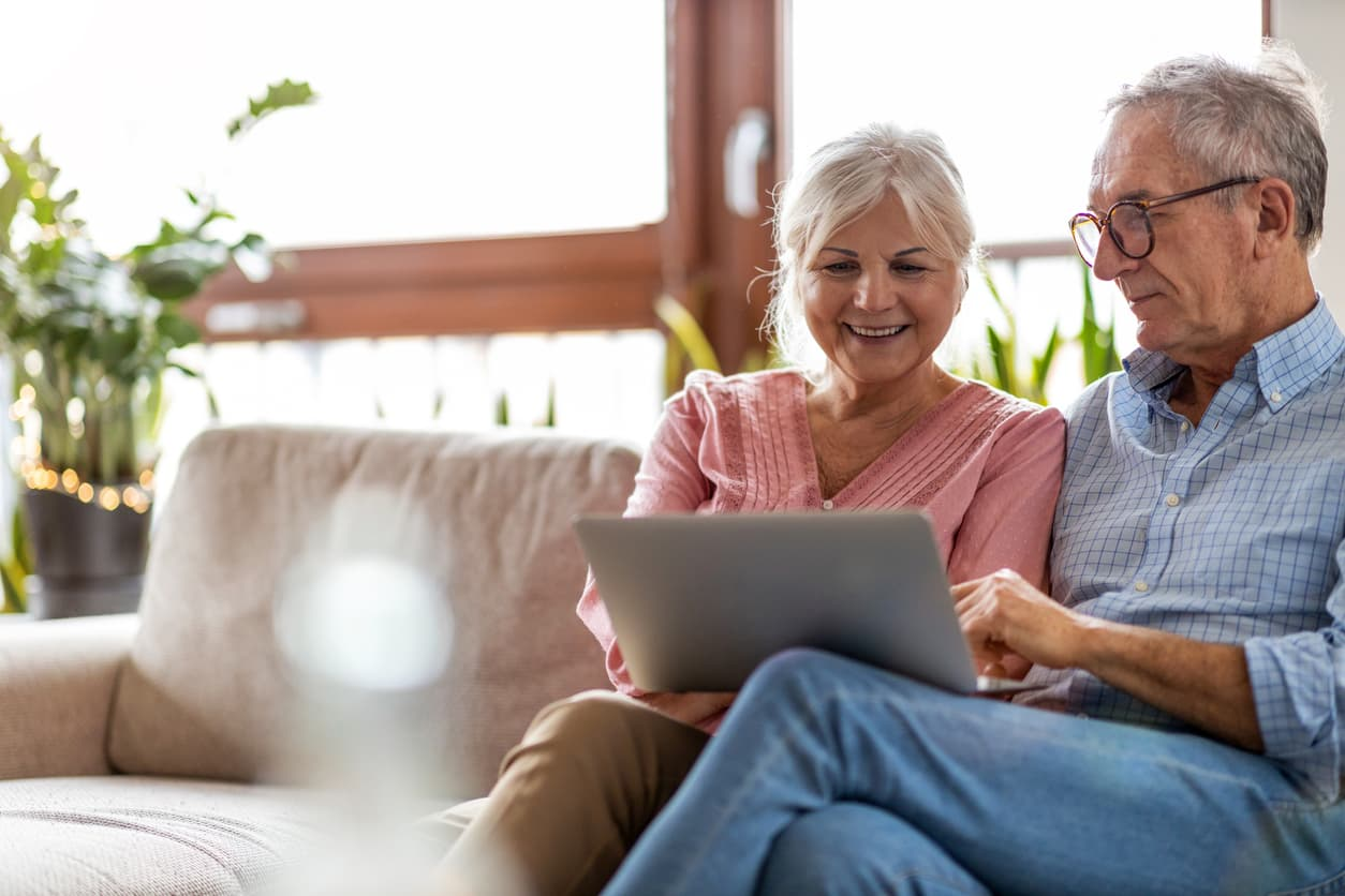 Senior couple using a laptop computer together at home.