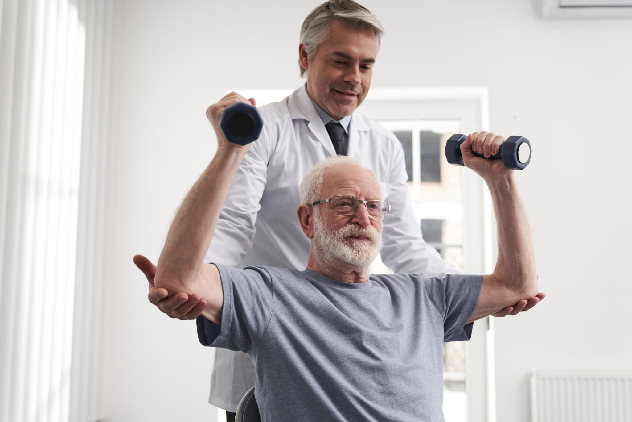 Older man doing arm exercises with weights and a therapist assisting.