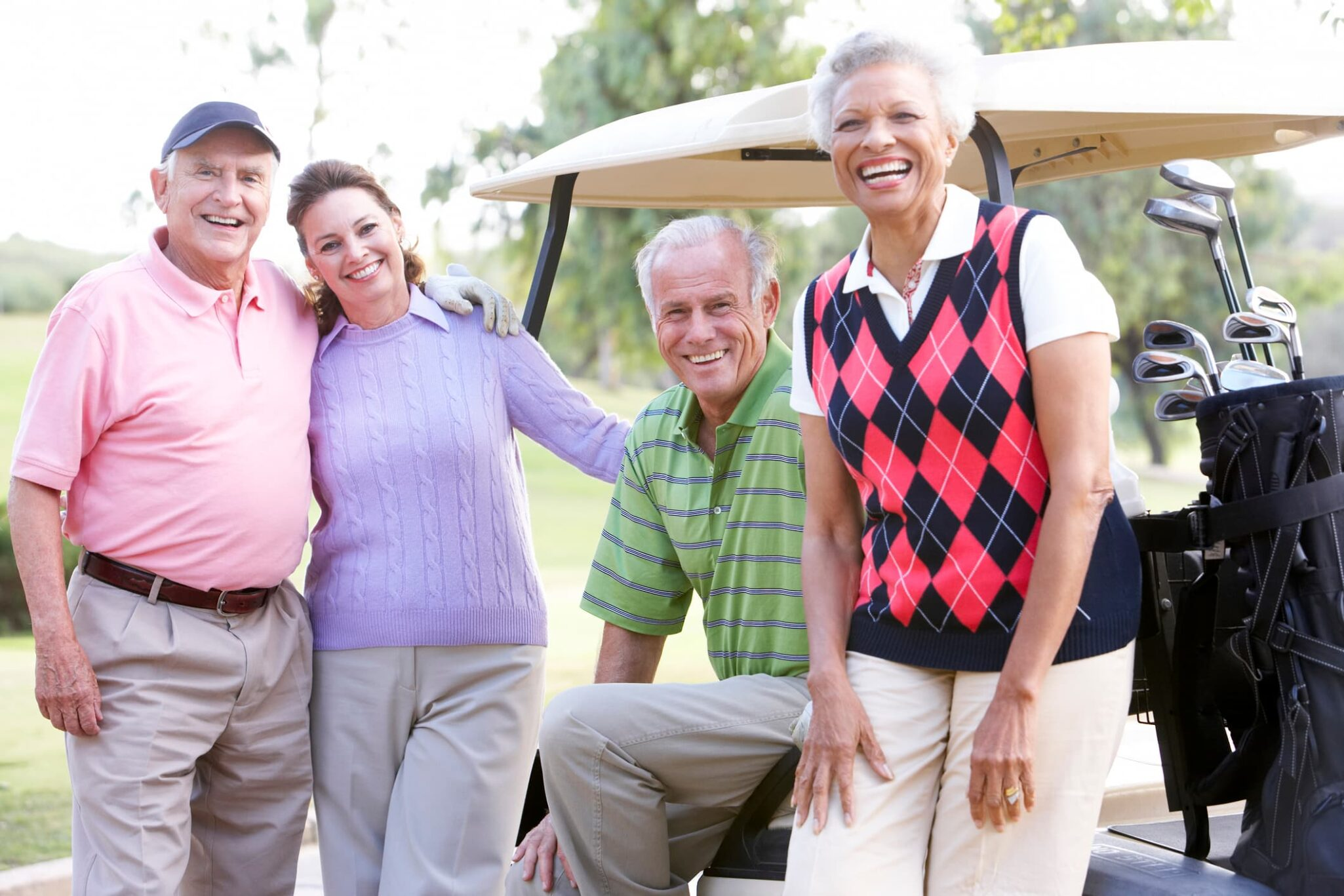 Four happy older adults having fun on the golf course