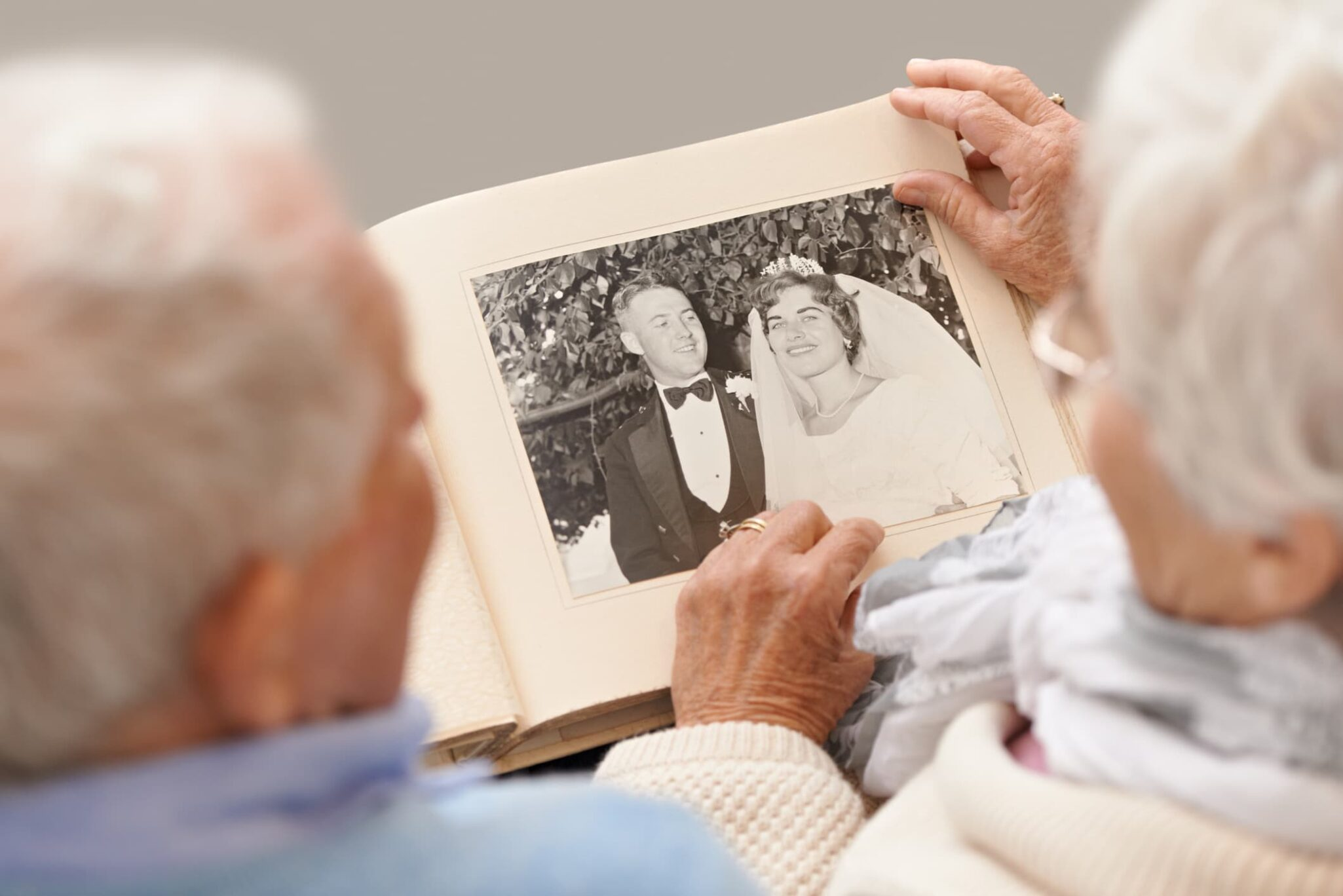 Older couple sitting on a couch together and looking at their wedding album.