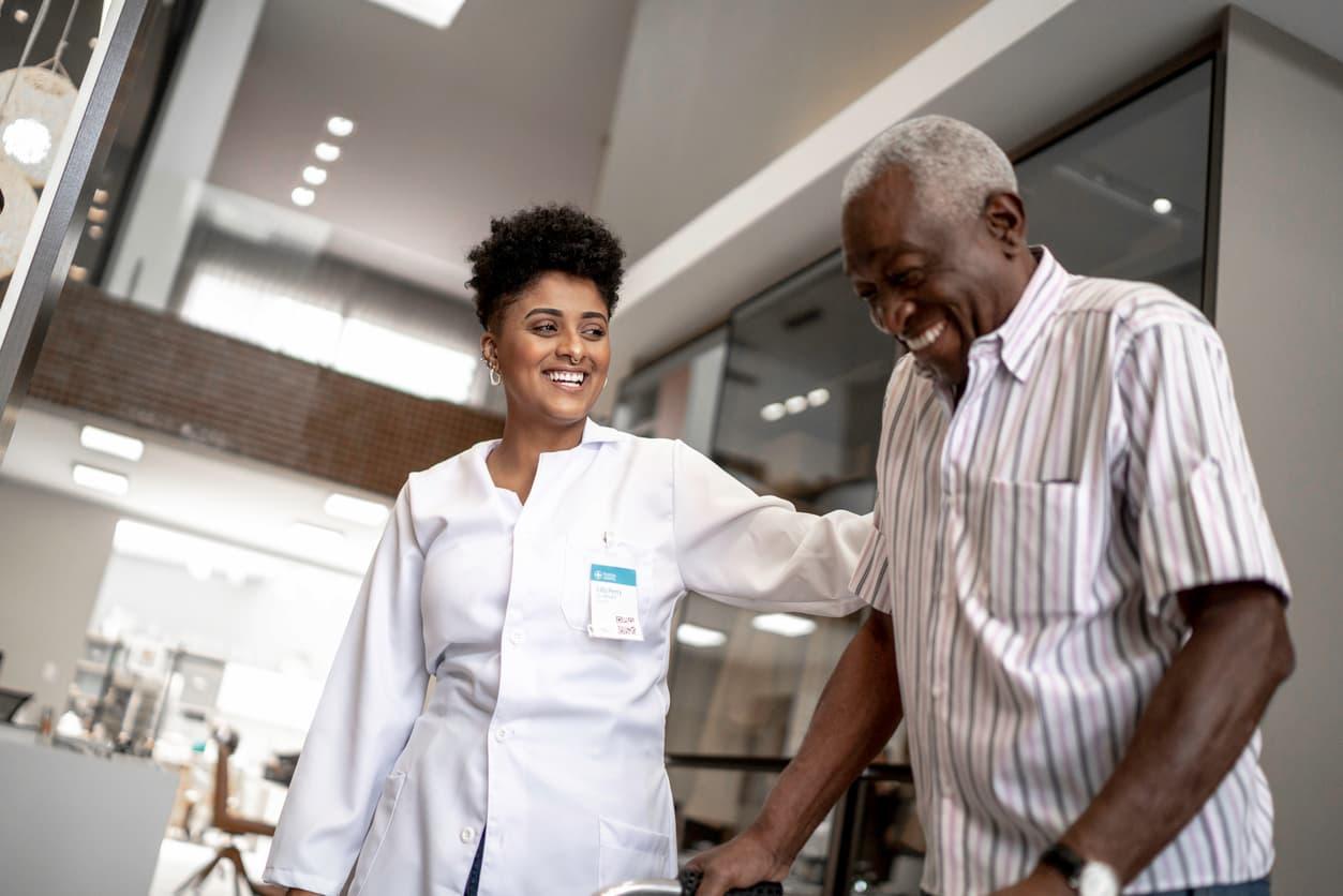Caregiver assisting senior man with walking.