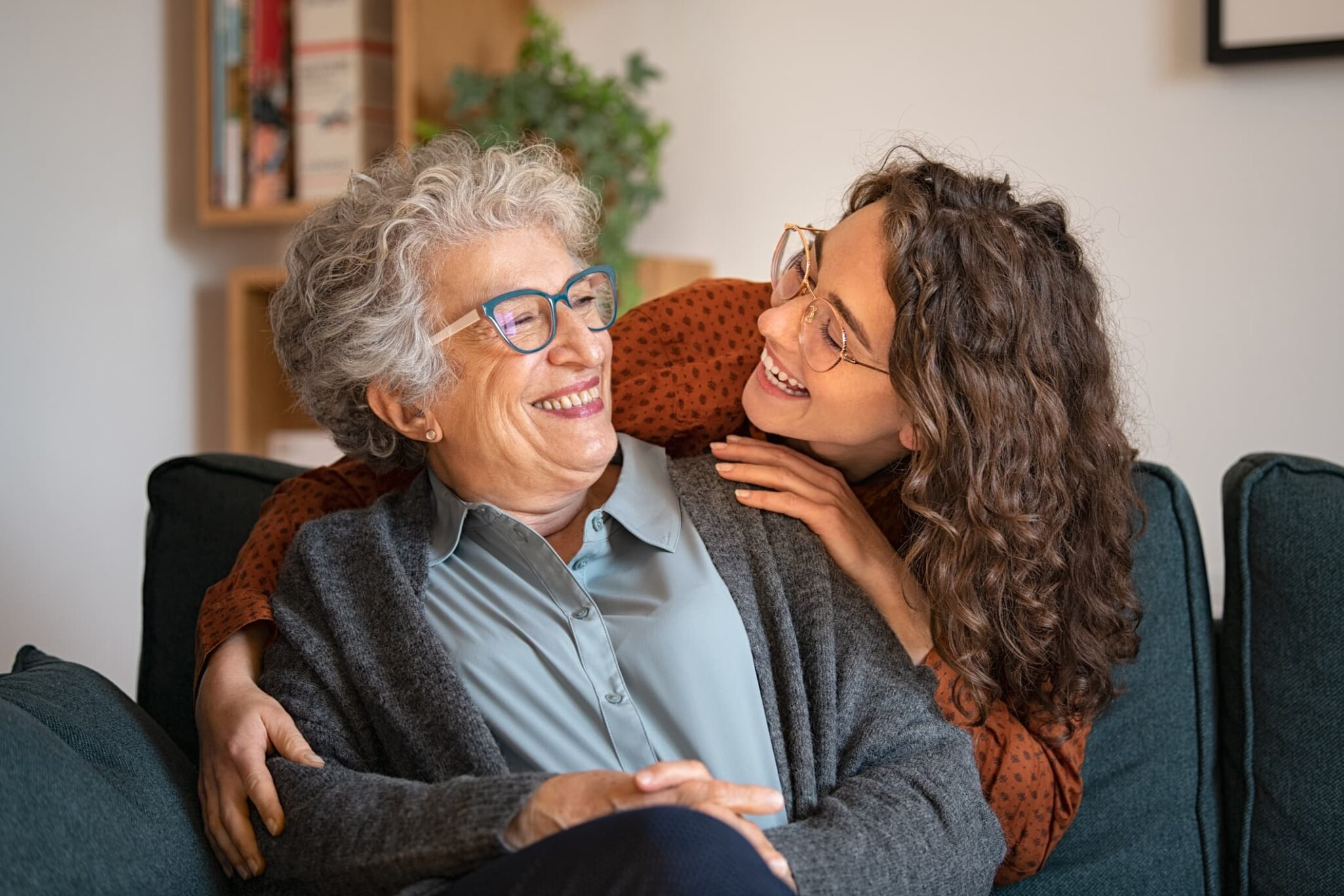 Older woman sitting on couch hugging adult child.