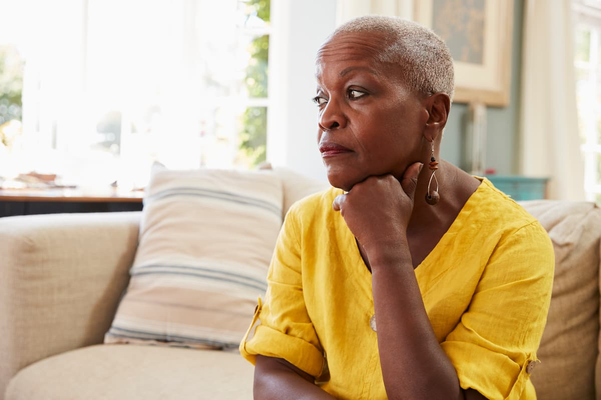 Stressed senior caretaker sitting on couch in thought.