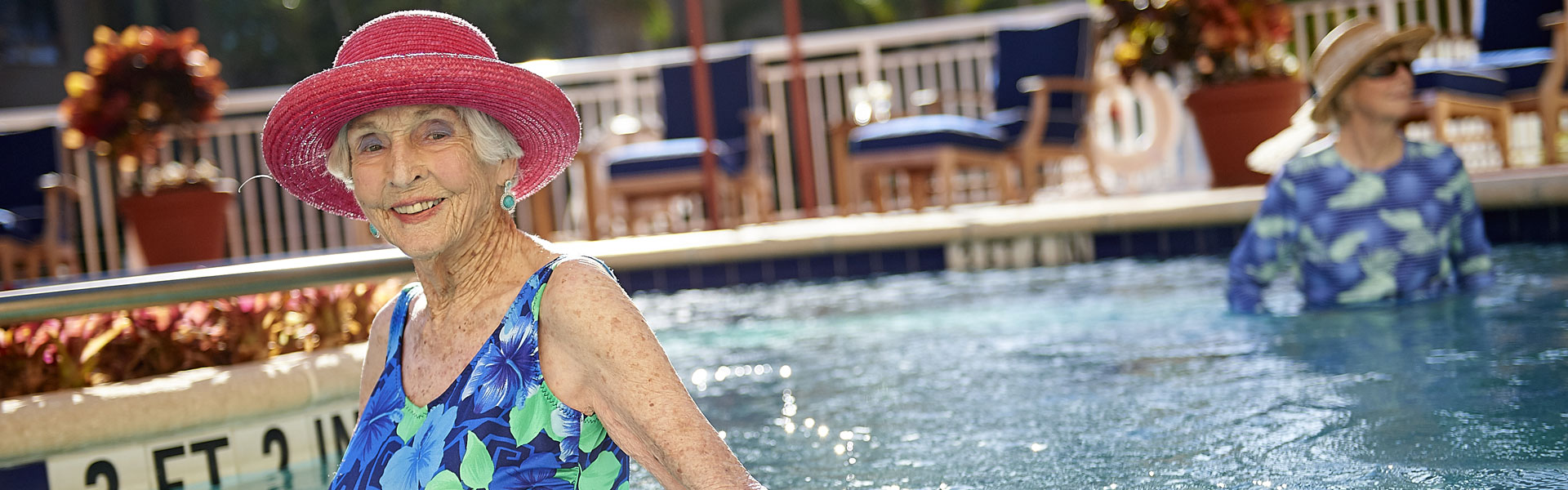 Two elderly women standing in the outdoor pool of their retirement community