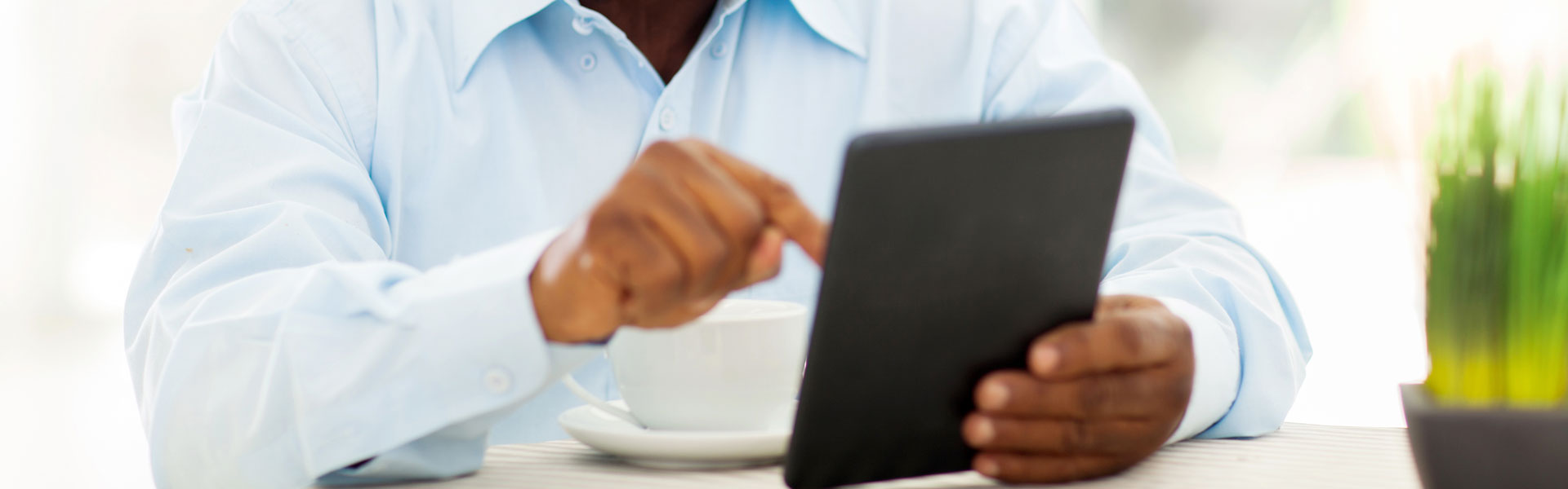 A man using a tablet and drinking coffee